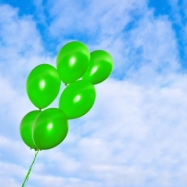 Image of green balloons against able sky background